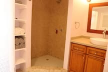The bathroom is large with a full shower and cabinets for hanging your clothes.