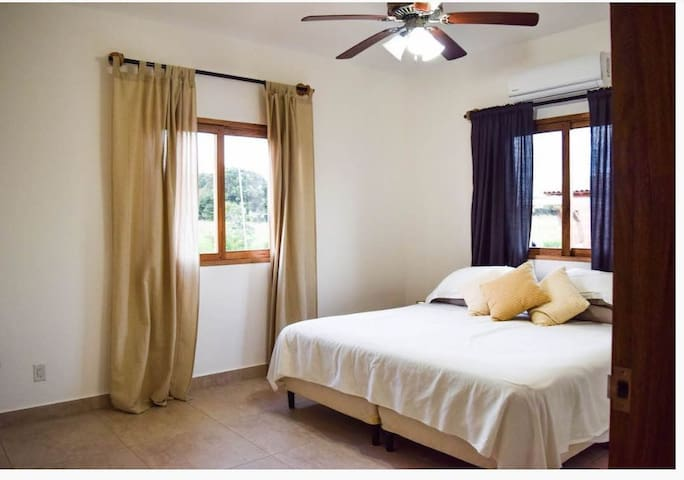 Master bedroom with a king size bed, a closet for hanging clothes and shelves. Private bathroom and a shower in the room. The room has AC unit, ceiling fans & mosquito net on the windows