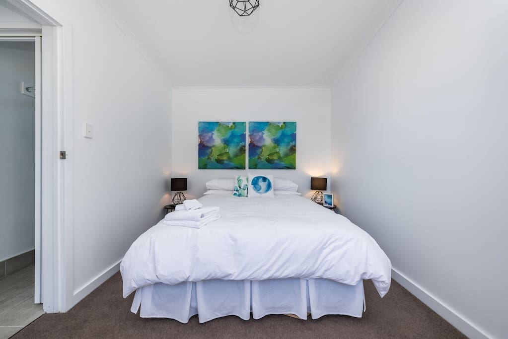 The main bedroom is a beautifully sunny room with a Queen bed and flat screen TV ......