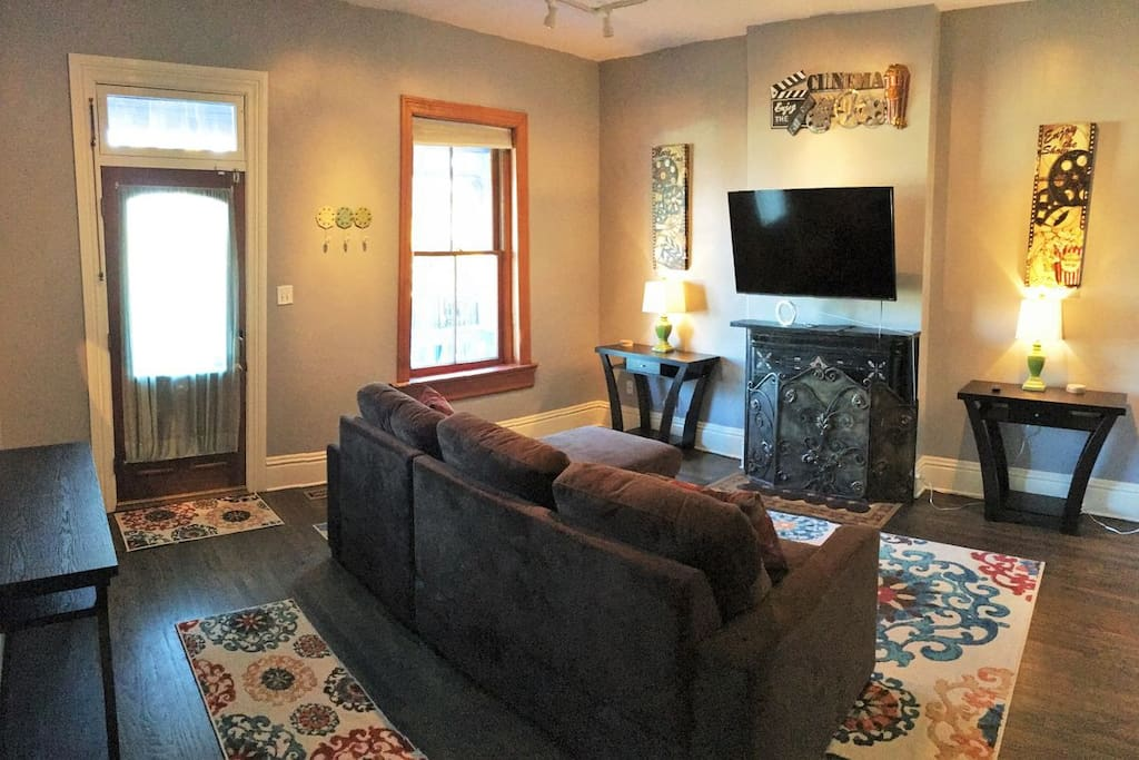 Large living spaces with a television & new furniture, and a foldout sofa-bed