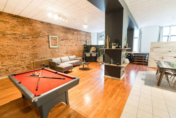 Pool table, living room, bar area, kitchen, and two sleeping areas on the platform by the windows.