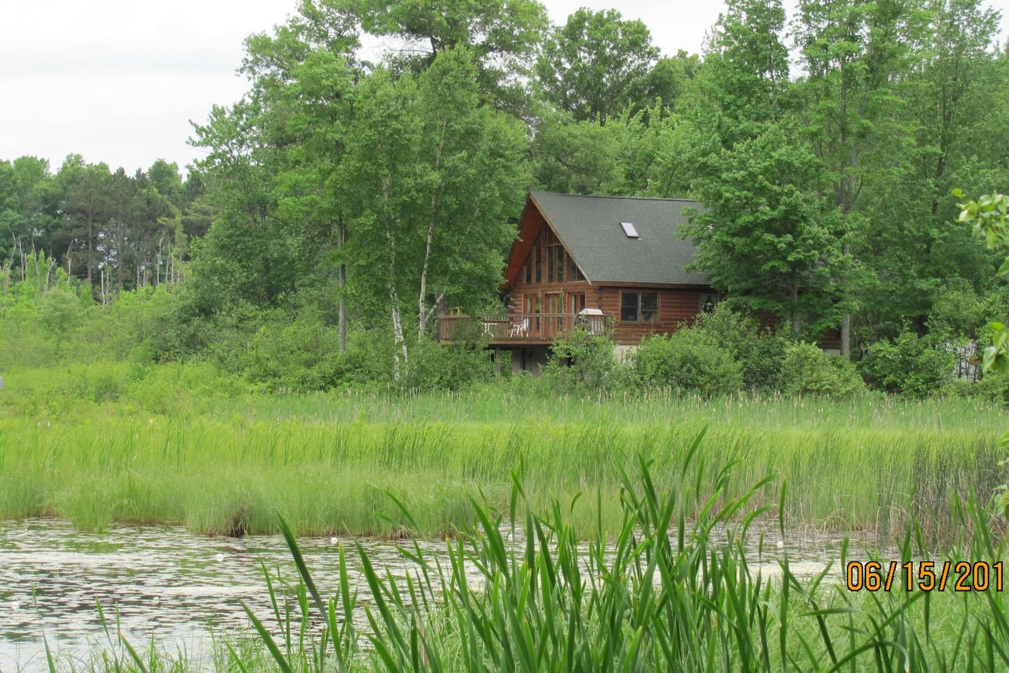 View of the cabin from the north across the marsh.  Lake is to the left.