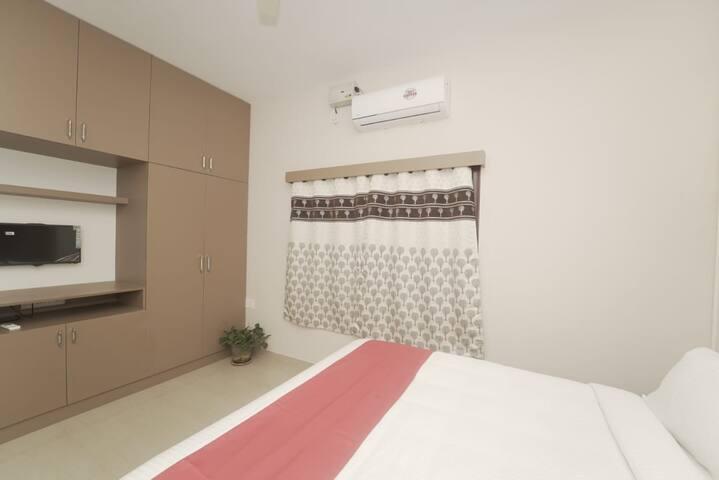 A cozy bedroom with a wide wardrobe