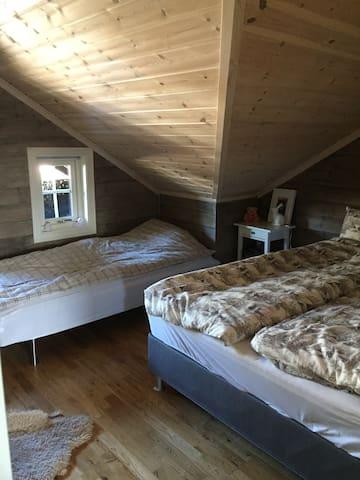Soverom med dobbelseng og en enkel seng i den øverste etasjen.