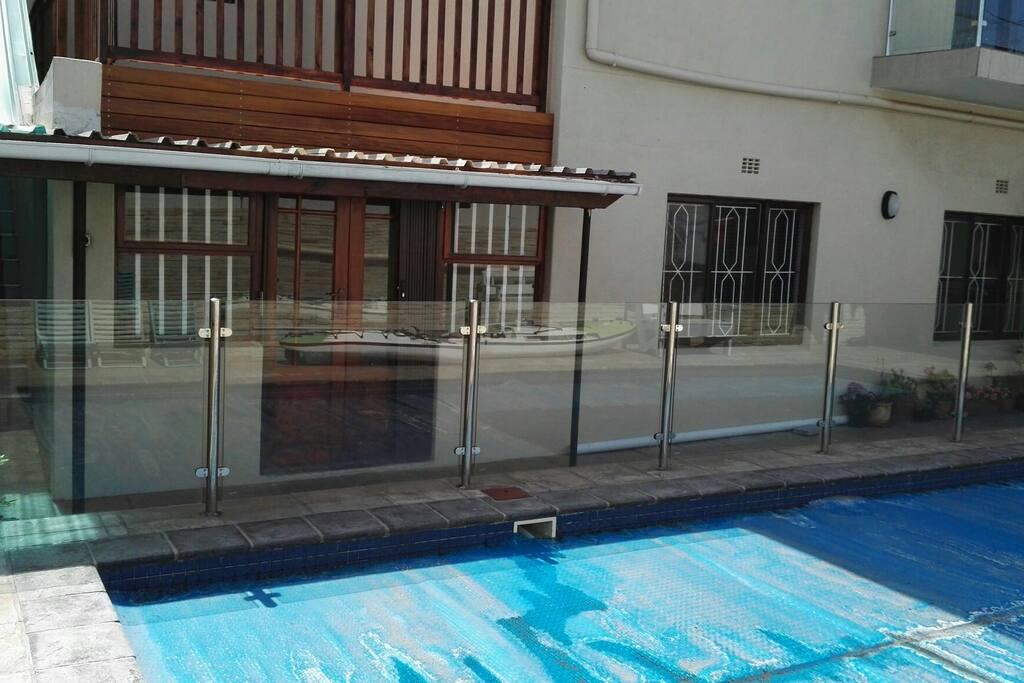 Swimming pool with secure glass enclosure