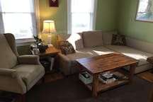 A cozy living room with a recliner, reading chair, pullout couch with chaise lounge, and TV