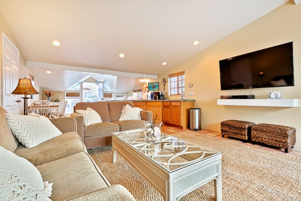 Large, light, bright Living Area with large wall mounted flat screen TV.