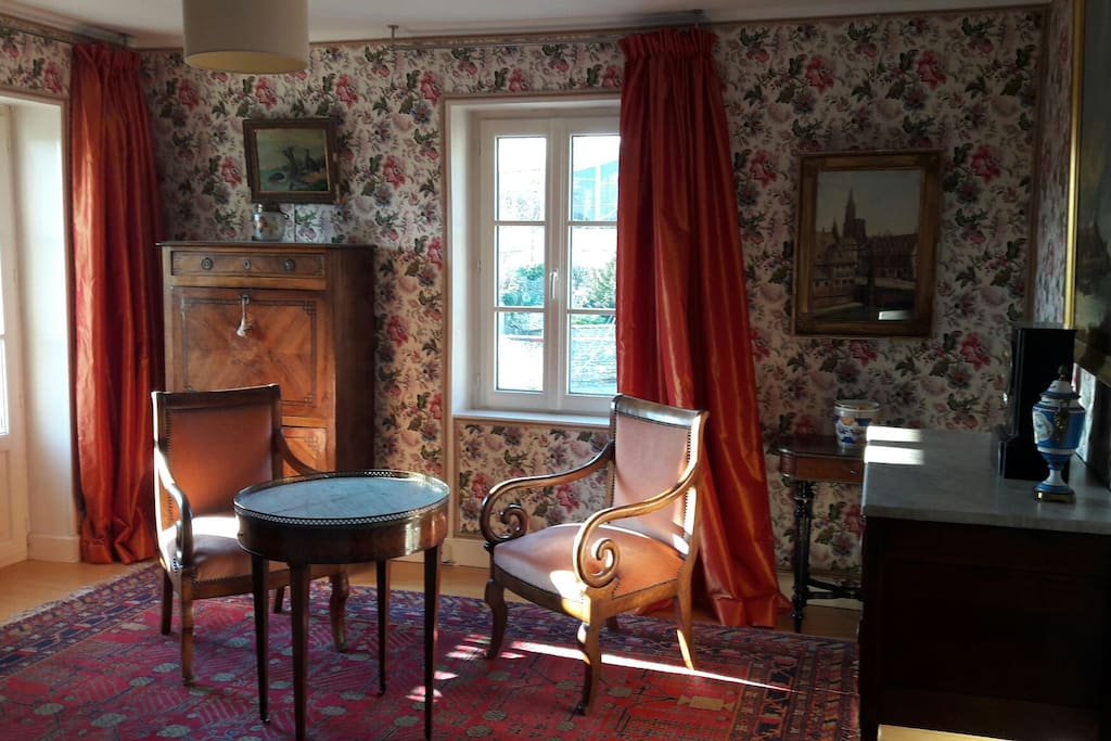 Bedroom with fabric lined walls and period furniture.