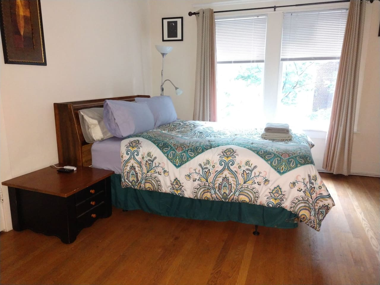 Full-size bed with reader light, night stand and headboard shelf