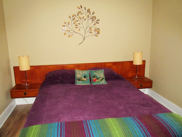 Back bedroom; mid-century feel with queen bed and fresh linens.
