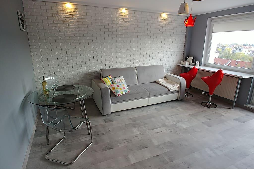 Nowoczesny salon z rozkładaną sofą, aneksem kuchennym i obłędnym widokiem na dachy Sopotu