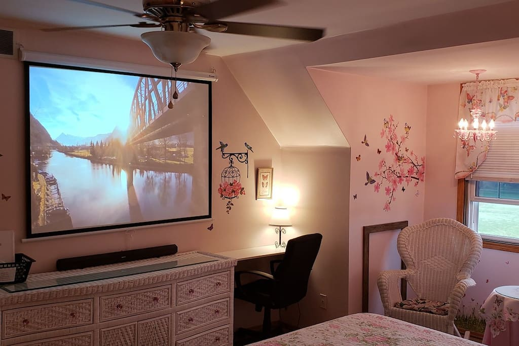"""Desk area with dresser, 53"""" projector and nook/sitting area"""