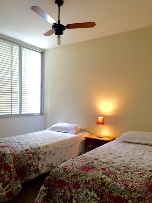 Quarto com ar-condicionado split, ventilador de teto, duas camas de casal que podem ser juntadas.