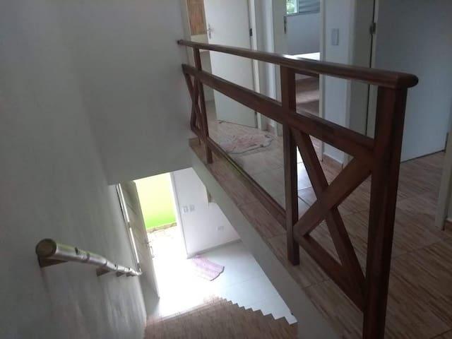 Vista de cima, para a porta de entrada, a esquerda, acesso aos quartos e banheiro.