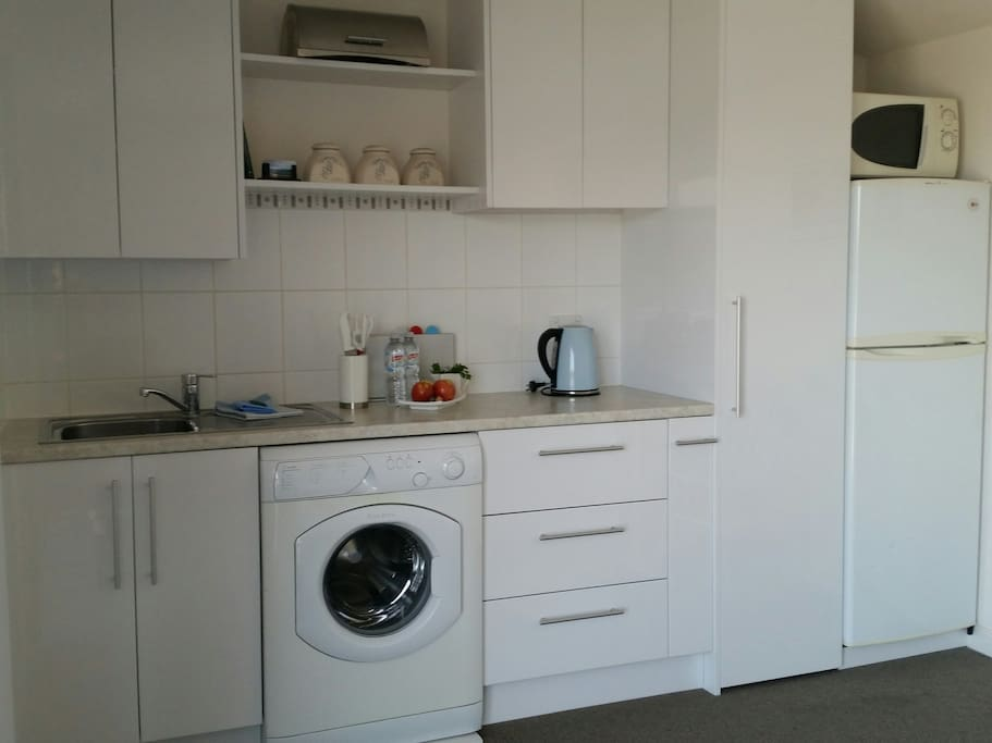 Kitchenette with sink,  fridge,front loading washing machine,pantry,toaster,slowcooker,sandwhich maker, electric kettle,microwave, crockery & cutlery. A double  electric hotplate and small oven are available in cupboard for making light meals.