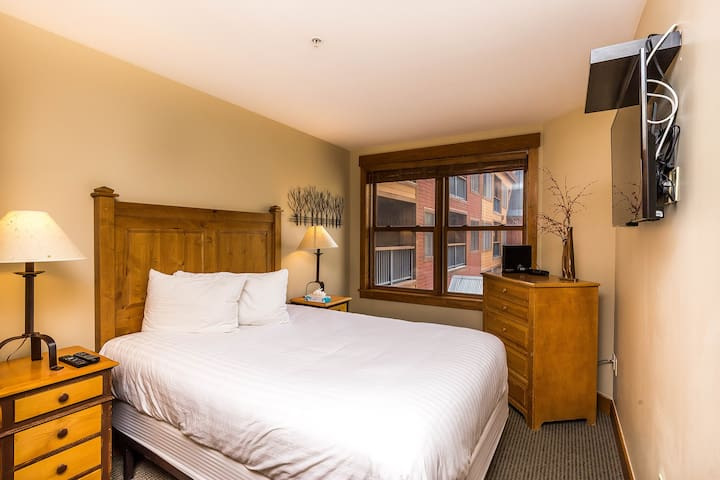 The master bedroom features a queen-sized bed with Ivory White Bedding and a mounted flat screen TV.