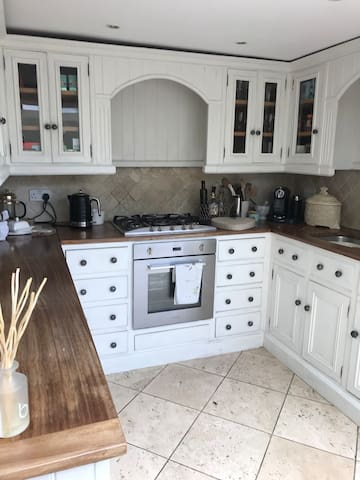 Fully equipped kitchen with handmade kitchen units.  With coffee machine, dishwasher, fridge and freezer.  Electric oven with gas hob with french doors leading to private courtyard with table and chairs.