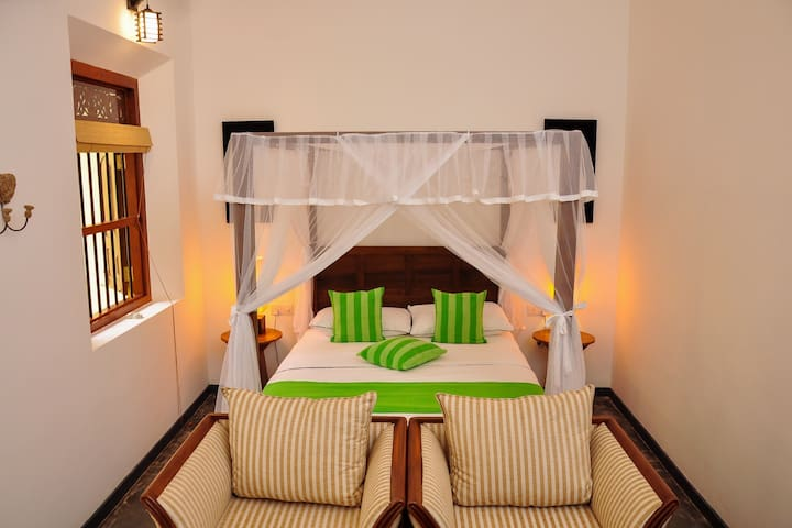 Our Master Suite four poster bedroom with comfy seating for two.