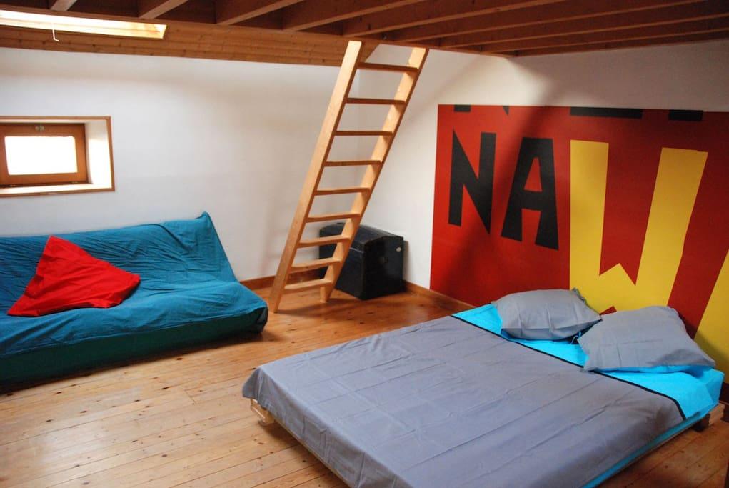 Vue de la chambre avec un lit supplémentaire sur mezzanine