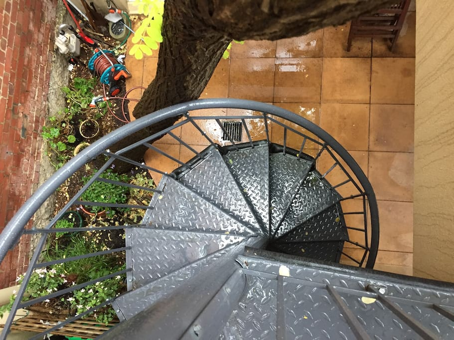 These spiral stairs are in our front courtyard and are quite narrow - but allow for you to come and go as you please .