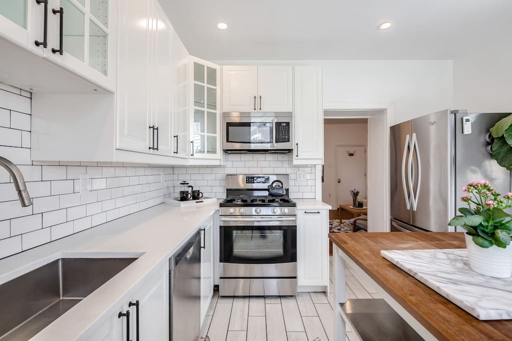 Kitchen with quartz countertops, gas range and oven, French press for coffee