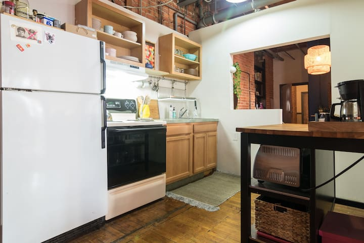 Fully stocked kitchen with a refrigerator, stove/oven, Aeropress, tea kettle and coffee maker.