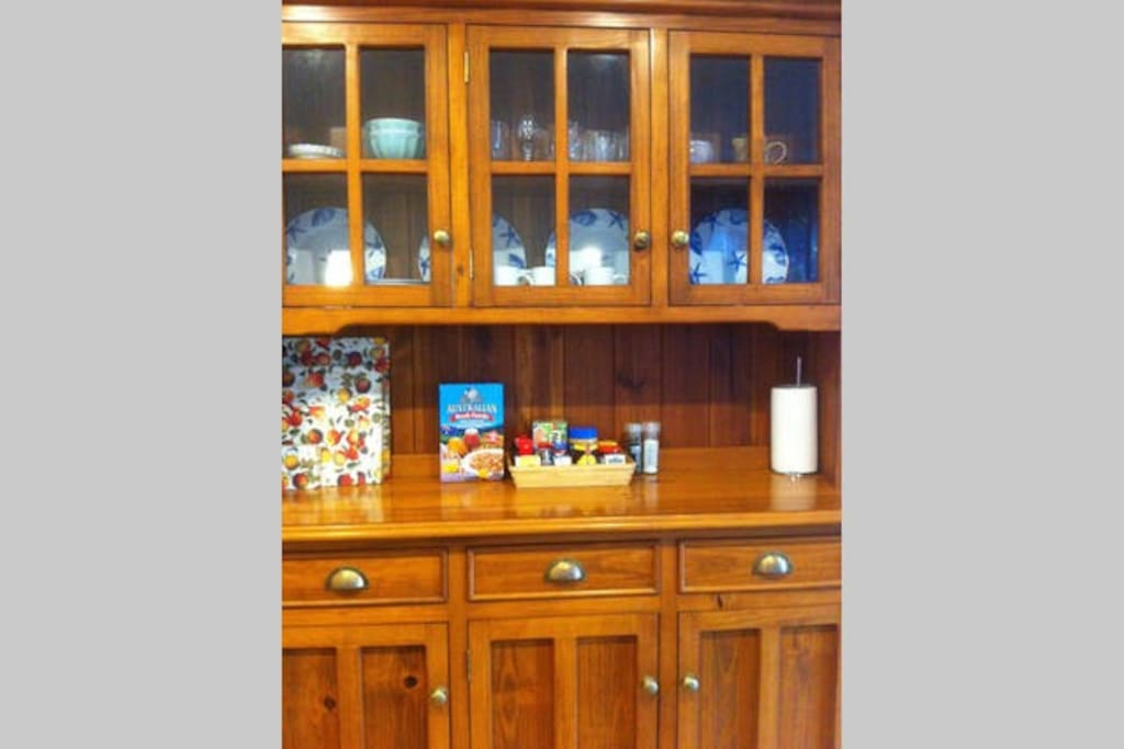 Cupboard contains breakfast foods, glasses, crockery, cutlery, paper towels, serviettes and steamer