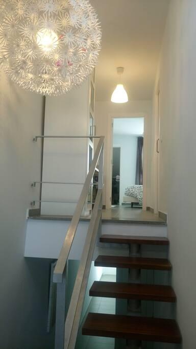 Escaleras hacia planta superior con dormitorio y baño