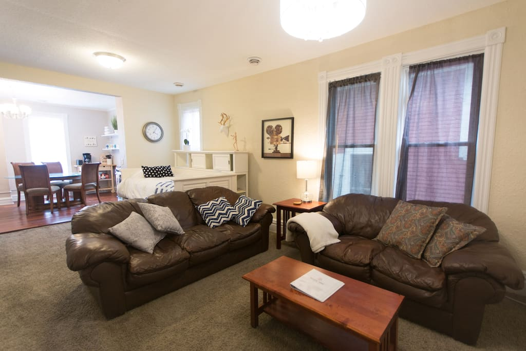 Large living room area with leather pull out couch, love seat, TV, and daybed with trundle