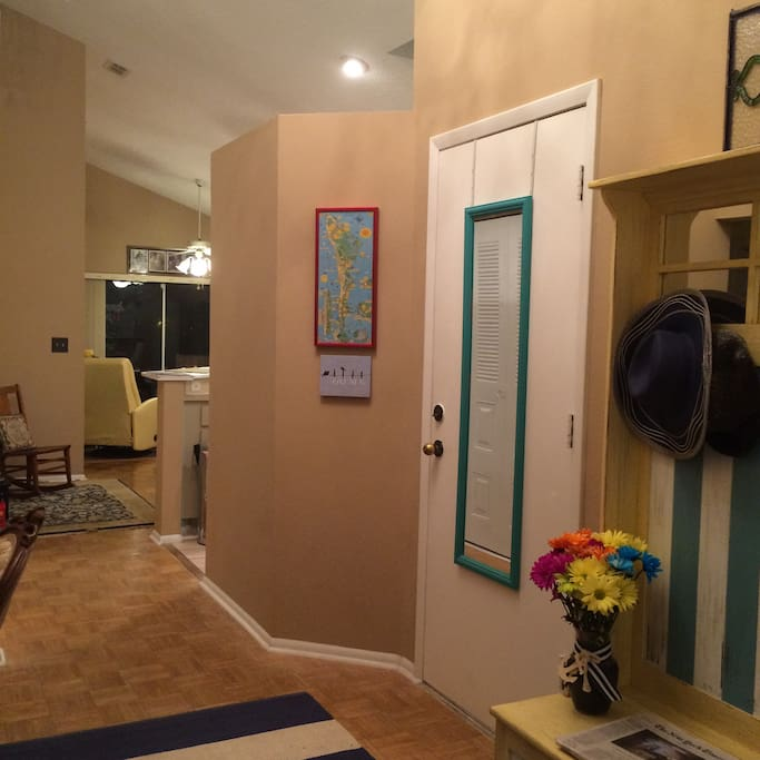 As you enter the house there is a desk to the left and a hall tree to the right. The laundry is behind the mirrored door.
