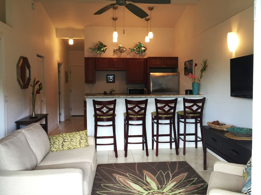 Full living room (shows TV on wall right side) and kitchen to the front door view from lanai