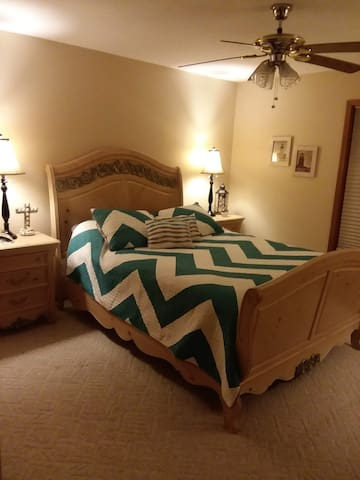 Spacious guestroom with closet, dressers and queensize bed.
