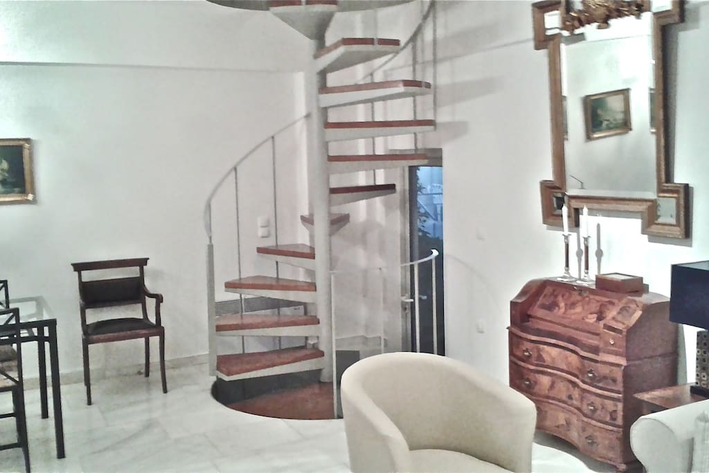 STUNNING SPIRAL STAIRCASE LEADS TO TWO OTHER LEVELS OF LIVING SPACE.