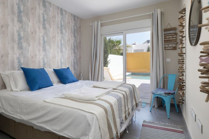 """Our second bedroom - The """" Nautical """" room . Ground floor with patio doors leading to pool . En-suite bathroom - large modern wardrobes and air con."""