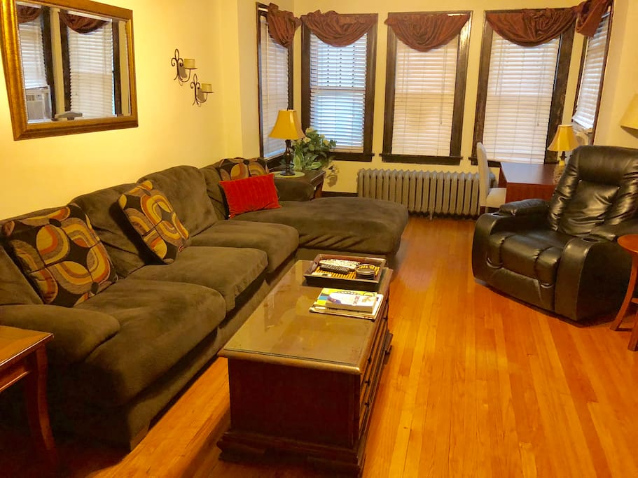 living room area with section couch, desk area and reclining chair