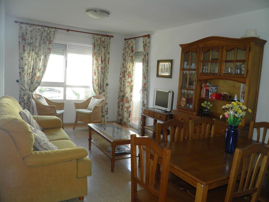 Salón con mesa de comedor para seis persona y acceso a la terraza