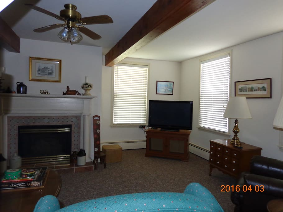 The spacious living room has exposed beams, ceiling fan, and TV with cable. Bright and cheery living space.