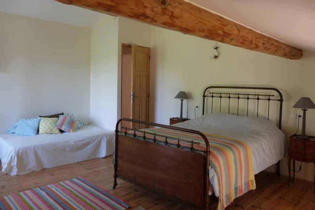 Chambre spacieuse avec poutre apparente, calme et lumineuse. Elle est équipée de : 1 lit double, 1 lit simple, une étagère, un bureau, 1 penderie.