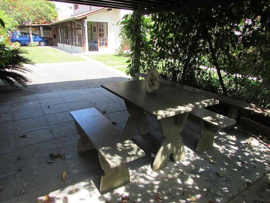 Carramanchão do jardim com mesa e bancos de pedra