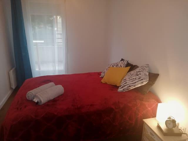 Chambre n°2 avec lit double, tables de chevet, lampes de nuit et réveil