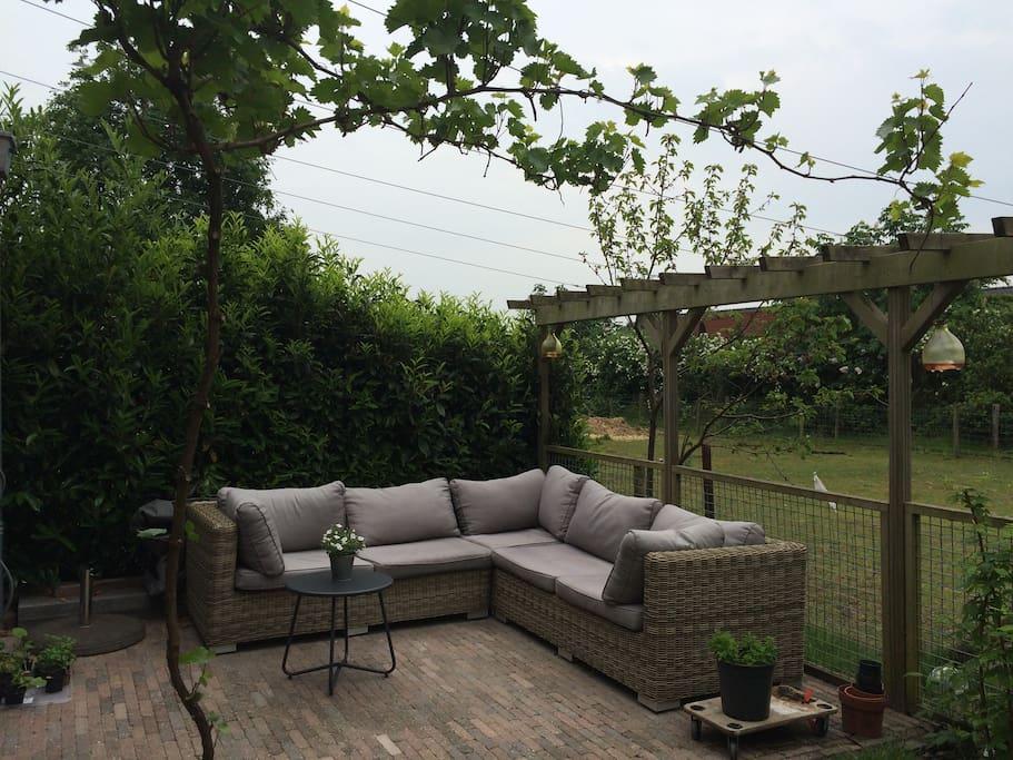 Heerlijke loungeplek achterin de zonnige tuin op het zuiden