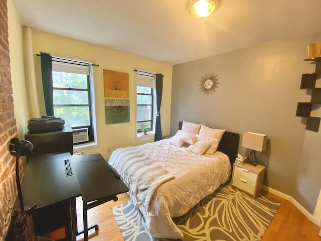 Spacious bedroom with plenty of light, luxury bedding experience and standing desk.   Standing desk is one of the two workstations in the apartment.   Standing desk could be lowered and turned into the regular sitting desk if needed.
