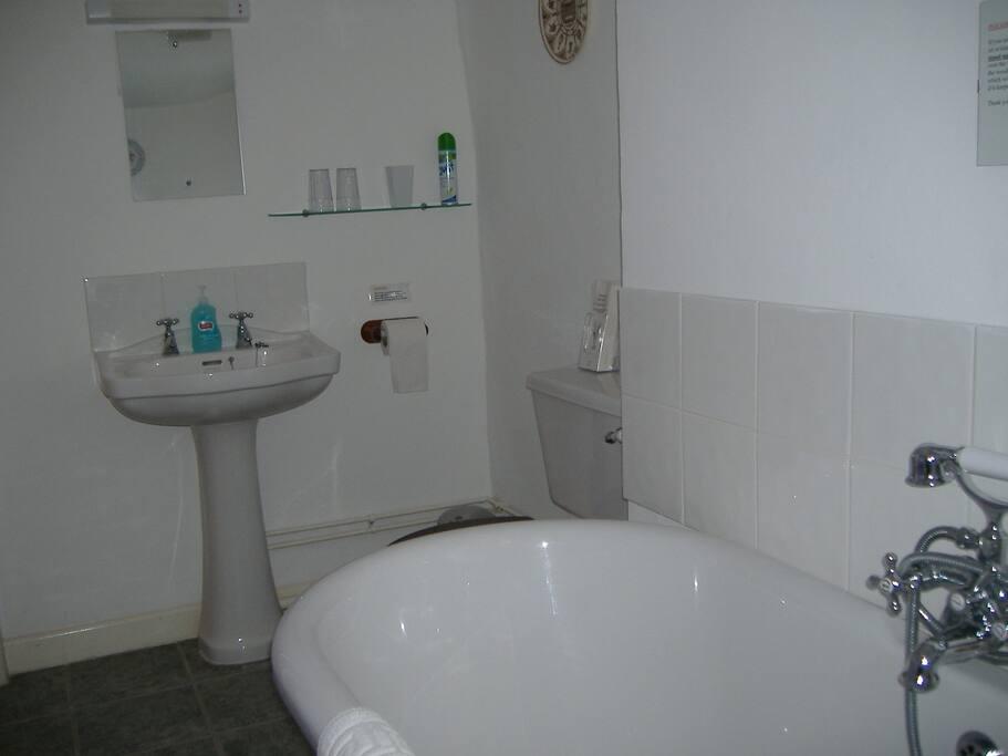bathroom with roll top bath