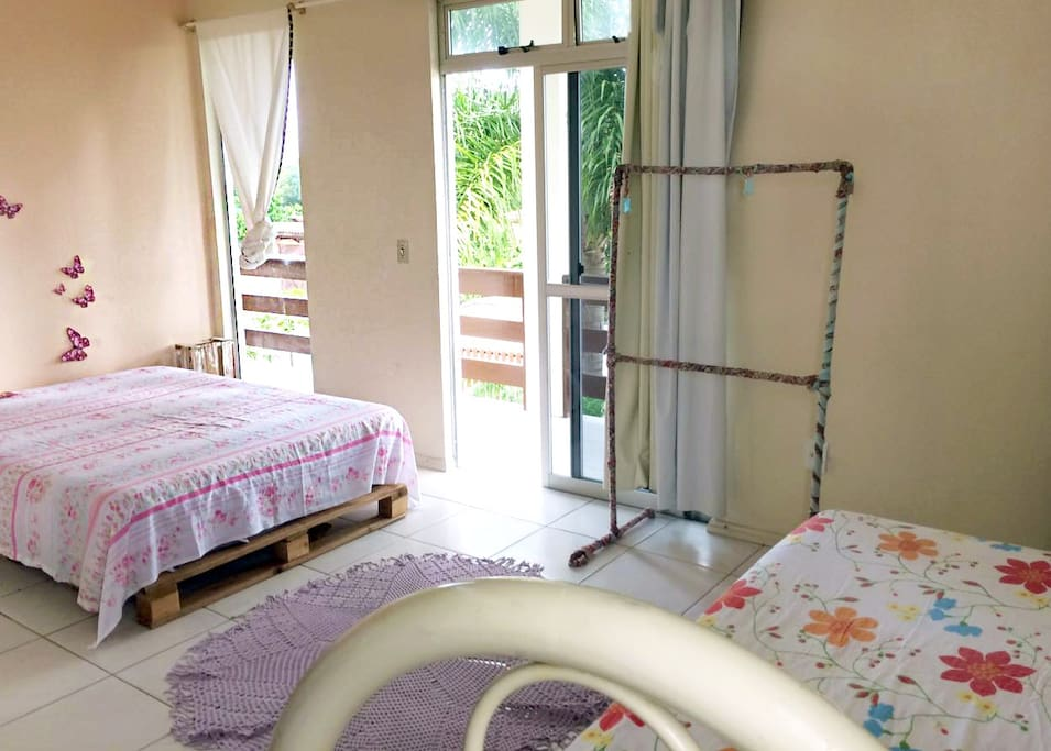 Suíte com varanda, cama de casal e cama de solteiro.