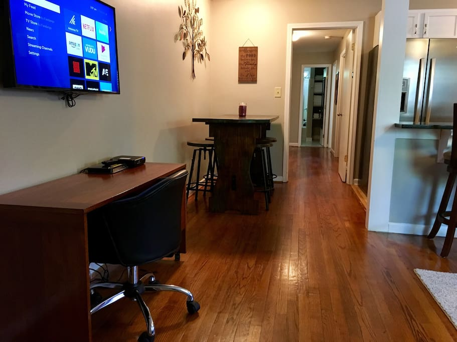 Smart TV, desk, dining table with stools  & hallway to bedrooms