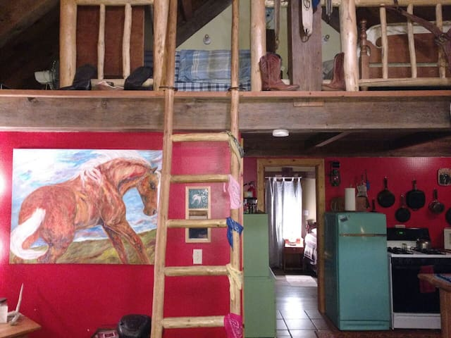 Lodgepole pine ladder access to upstairs sleeping loft. Paintings by local artist, Candy Brennan.