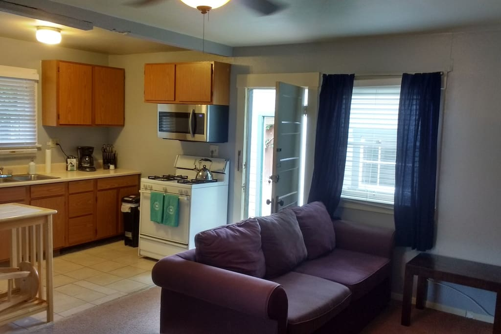 Another view of kitchen with entrance and living area.