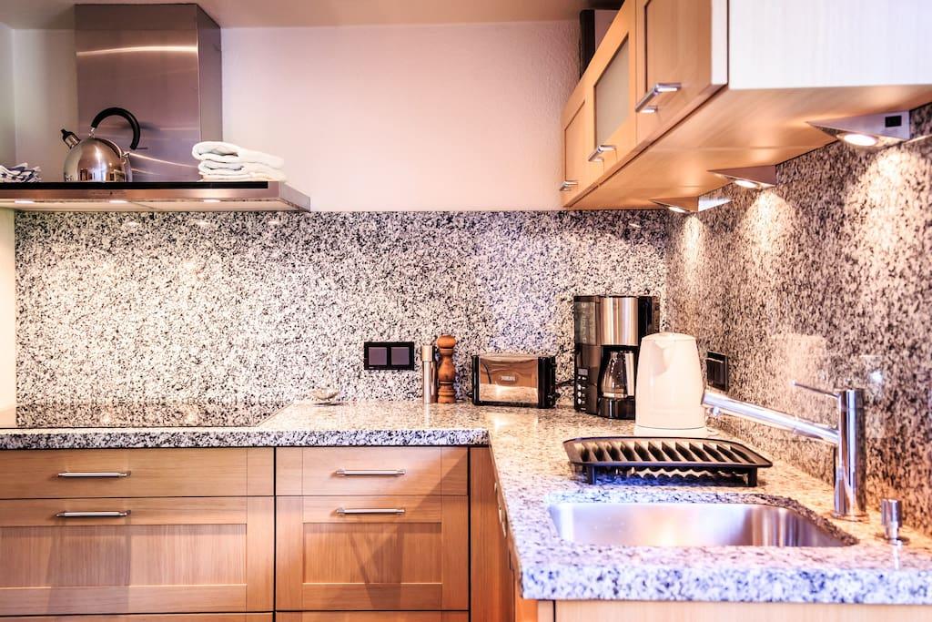 Die linke Seite der Küche mit dem 80 cm Induktions-Kochfeld, Dunstabzugshaube, Kühlschrank und Spülmaschine