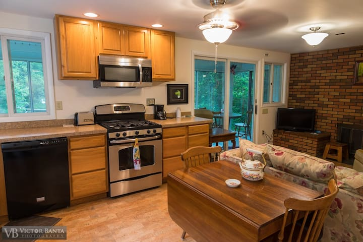 The kitchen/dinning room area has a sliding glass door with view of the lake and allows access to the 3 season room with views of the lake and woods.