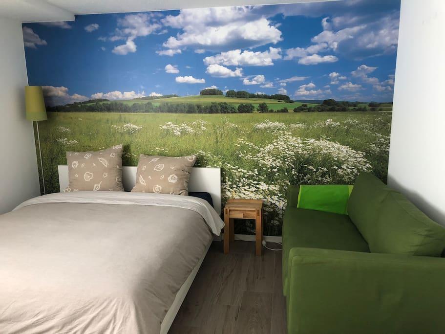 Das Bett (für 2 Personen), 160x200 cm, rechts davon ein kleiner Beistelltisch und ein Sofa